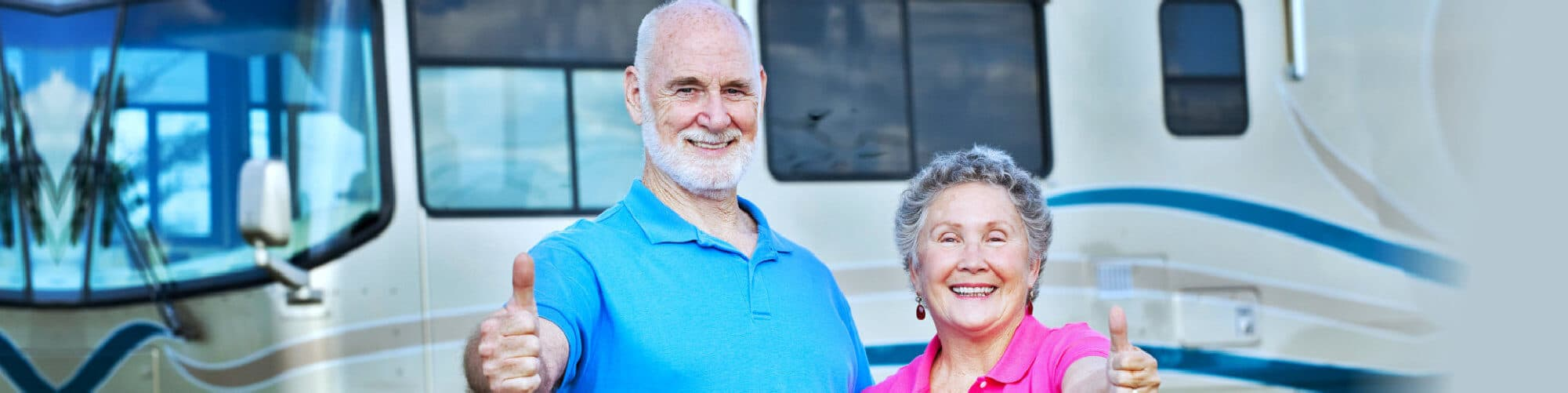 Senior couple posing in front of their luxury motor home, giving a thumbs