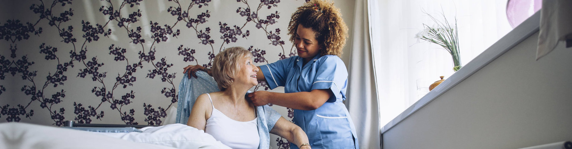 old woman assisted to her caregiver at the bed