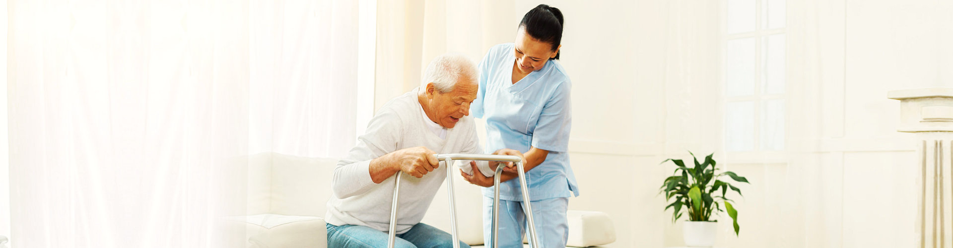 old man assited to her caregiver to stand and walk